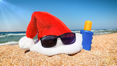 Closeup image of Santas hat and sunglasses on the beach. Concept of travel and tourism on Christmas, New Year and winter holidays.