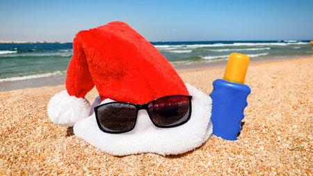 Closeup image of Santas hat and sunglasses on the sea beach. Concept of travel and tourism on Christmas, New Year and winter holidays.