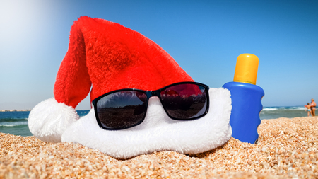 Closeup image of Santa Claus cap with sunglasses and sunscreen lotion on the beach at hot sunny day. Concept of travel and tourism on Christmas, New Year and winter holidays. Stock Photo