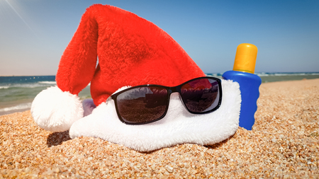 Closeup photo of Santa's hat with sunglasses and sun lotion on sandy sea beach. Concept of travel and tourism on Christmas, New Year and winter holidays.