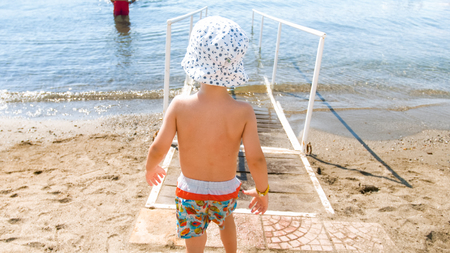 Rear view photo of little toddler boy walking in the sea