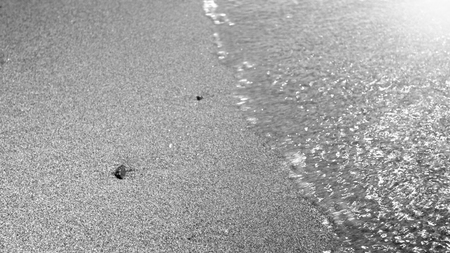 Black and white macro image of wet sand on the sea beach and calm waves