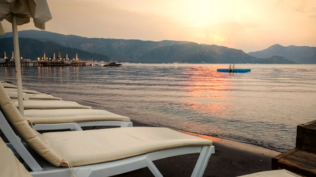 Sea beach with rows of sunbeds at the sunset Stockfoto