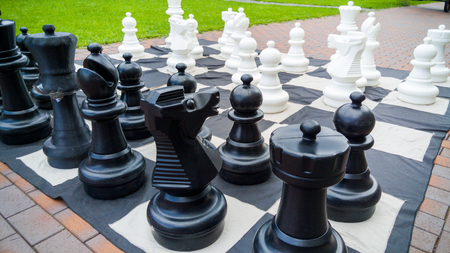Closeup image of giant chessboard and chess figures in park. Entertainment and fun for family outdoors