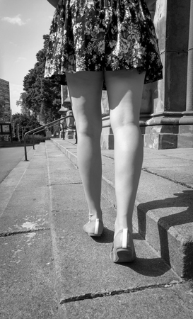 Black and white photo of beautiful slim female legs in ballet flats and short dress walking on street