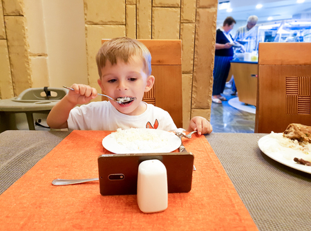 Portrait of boy watching cartoons on smartphone while eating in restaurant or cafe Banco de Imagens