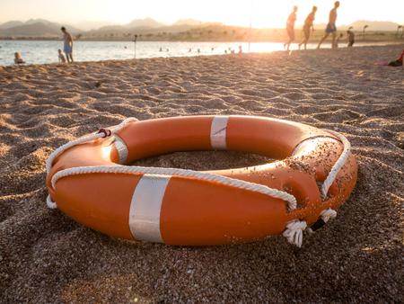 Image en gros plan d'un anneau de sauvetage en plastique rouge sur le sable de la plage de la mer contre un beau coucher de soleil sur l'océan