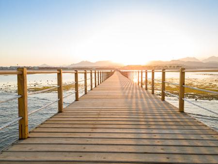 Schönes Bild des langen hölzernen Piers oder der Brücke im Ozean Standard-Bild