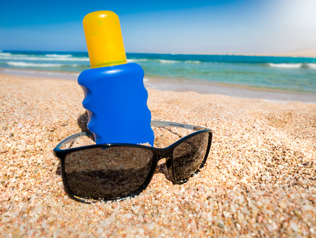 Closeup shot of UV sun protection lotion in blue bottle and sunglass lying on the sandy beach at sea. Perfect image for illustrating summer holiday vacation.
