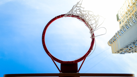 Closeup photo of basketball ring with net against blue sky and high building in city living district