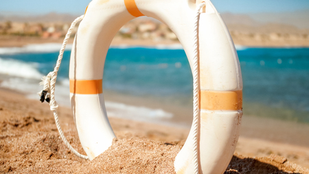 Landscape of sandy sea beach and white plastic life saving ring. Perfect shot to illustrate summer holiday vacation at ocean.