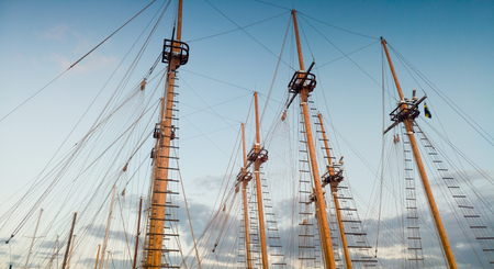 Photo of high wooden masts of old ships in port against blue sky at evening Stock Photo
