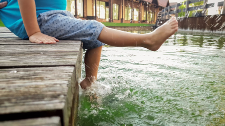 Closeup image of 3 years old little boy sitting on the wooden pier and holding his feet in river water. CHild splashing in lake with legs