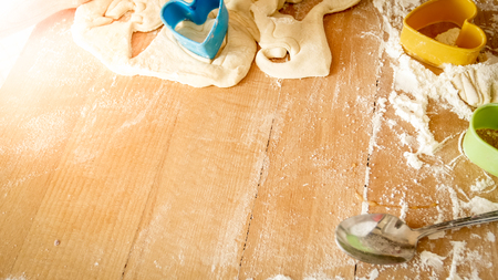 Closeup image from high angle on wooden desk covered with flour, dough, cooking tools and ingredients for cooking and baking at kitchen