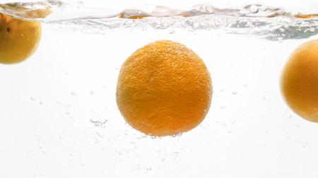 Closeup photo of fresh ripe oranges falling and splashing in water against white background Stock Photo