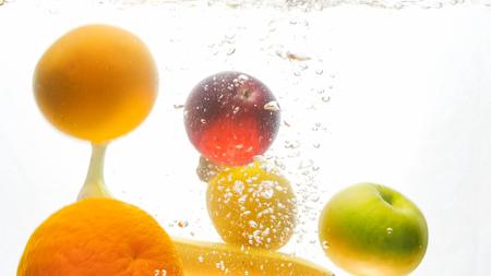 Closeup photo of lots of tasty fresh juicy fruits falling in water and splashing