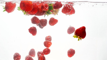 Closeup photo of mixed berries falling and spalshing in water. Lots of raspberries and strawberries floating in water against white background