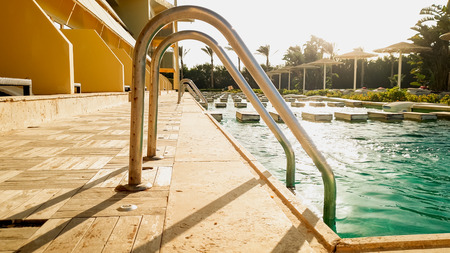Beautiful image of outdoor swimming pool with turqouise clean water at summer vacation hotel resort