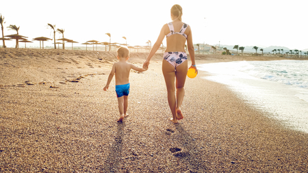 Photo of happy young mother with adorable 3 years old toddler boy holding hands and walking on the sea beach against beutiful sunset sky over the water surface.