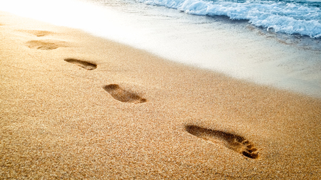 Closeup beautiful photo of human footprints on wet sand at sea beach against beautiful sunset over the water surface