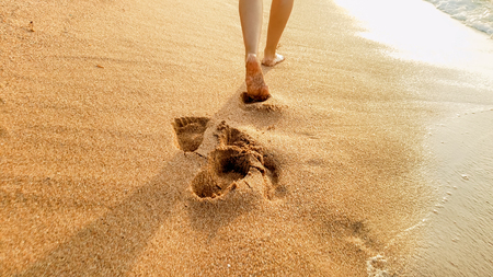 Closeup photo of barefoot female feet walking on the wet sand and calm warm waves at sea beach