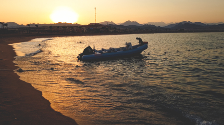 Beautiful photo of inflatable motorboat floating on sea waves against beutiful sunset