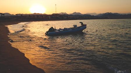 Schönes Foto von aufblasbarem Motorboot, das auf Meereswellen gegen schönen Sonnenuntergang schwimmt