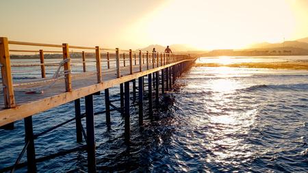 Amazing sunset over long wooden pier in calm ocean. Sea waves rolling on breaking on the wooden bridge 免版税图像