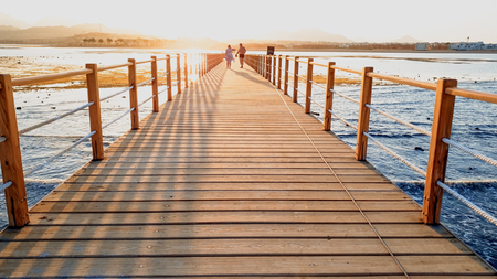 Beautiful landscape of calm ocean waves and wooden pier. Amazing jetty at sea aagainst sunset over the mountains