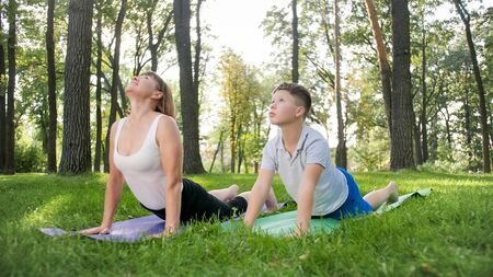 Photo of middle aged woman with 12 years old teenage boy practising yoga and meditating at park. family relaxing and doing fitness at nature