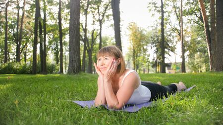 Image of mid aged smiling happy woman meditating and doing yoga exercises on grass at forest. Woman taking care of her physical and mental health while pracitising fitness and stretching at park Stok Fotoğraf
