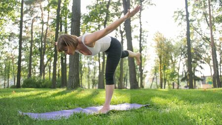 Image of smiling middle aged woman in fitness clothes doing stretching and yoga exercises. WOman meditating and doings sports on fitness mat on grass at park