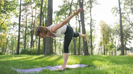 Photo of middle aged woman practicing yoga or fitness on fresh green grass at park. Female physical and mental health. Person in meditation and harmony pf body and soul Stok Fotoğraf