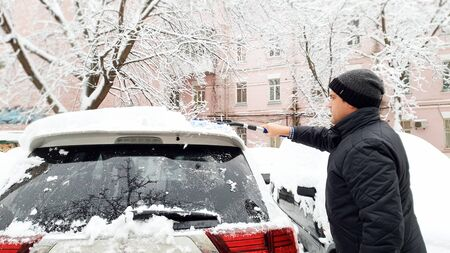 Photo of young handsome man in black coat and hat trying to clean up snow covered white car after blizzard with brush