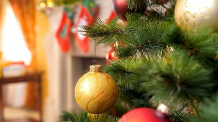Closeup image of Christmas tree branch decorated with garlands and golden baubles against firepalce with socks for Santa gifts