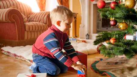 Portrait of happy smiling boy taking toys of Christmas gift box and playing on floor under Christmas tree Stock Photo