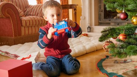 Happy little boy looking and smiling at toy train he got on Christmas. Child recieving presents on New Year