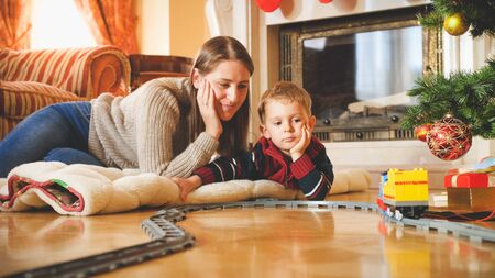 Toned portrait of family enjoying Christmas morning and playing with toy railroad. Child receiving presents and toys on New Year or Xmas 스톡 콘텐츠