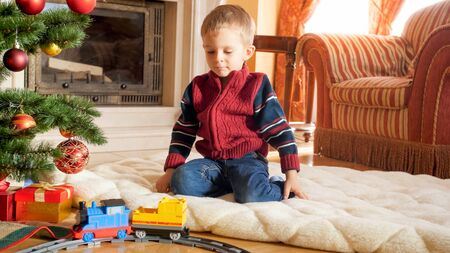 Portrait of little boy sitting on floor and playing with toy railroad that Santa gave him for Christmas. Child receiving presents and toys on New Year or Xmas Stock Photo