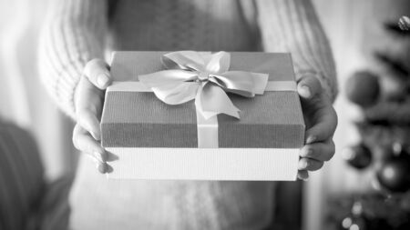 Closeup black and white image of female hand holding beautiful box with present tied with silk bow ribbon
