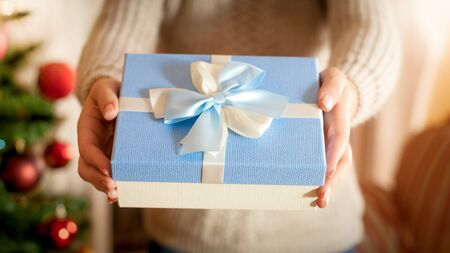 Closeup photo of young woman standing at Christmas tree and giving blue present box with silk ribbon bow. Perfect image for winter holidays and celebrations