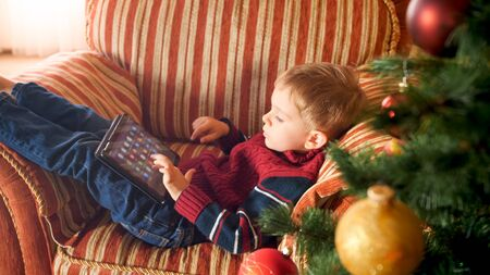Portrait of little boy with digital tablet computer playing games or browsing internet. Child in house on Christmas morning