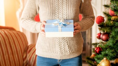 Closeup image of young woman holding blue box with ribbon bow against Christmas tree in living room