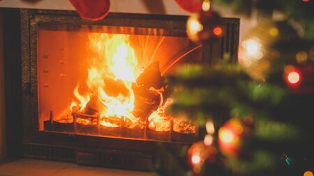 Beautiufl toned image of burning fireplace next to decorated Christmas tree with baubles and garlands