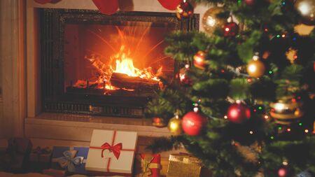 Getinte kerstachtergrond met kerstcadeaus en cadeautjes onder de kerstboom en brandende open haard Stockfoto