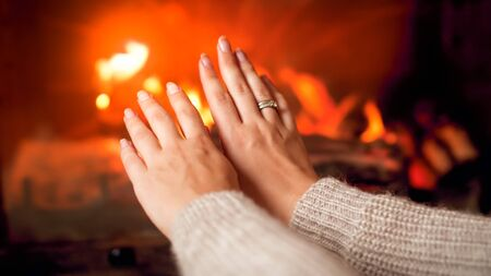 Closeup image of young woman in sweater warming her hands at burning fireplace at house