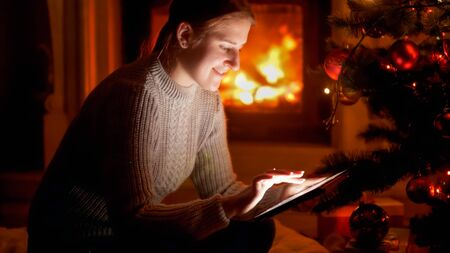 Portrait of smiling young woman sitting next to Christmas tree and typing message on tablet computer