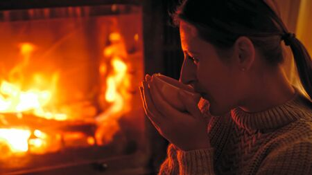 Closeup toned image of young woman drinking tea at night while sitting by the burning fireplace at house