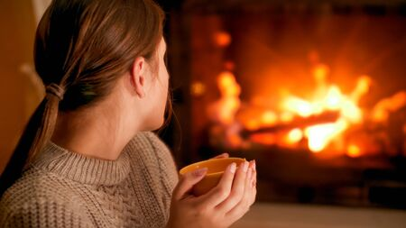 Portrait of woman in woolen sweater holding cup of hot tea and looking at burning firepalce