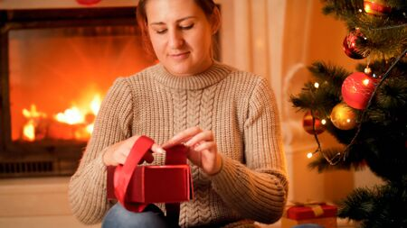 Portrait of young woman in sweater sitting next to burning firepalce and packing Christmas gifts and presents 스톡 콘텐츠